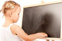 Bambina che si leva in piedi alla lavagna Fotografia Stock