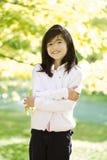 Bambina che si leva in piedi fra i fogli di autunno luminosi Fotografie Stock