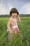 Bambina che si leva in piedi nell'erba del prato. immagine stock