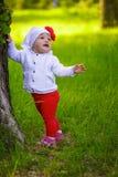 Bambina che si leva in piedi vicino ad un albero Fotografie Stock