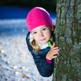 Bambina che si nasconde dietro un albero nel parco Fotografia Stock
