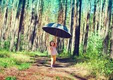 Bambina che si nasconde sotto il grande ombrello nero immagine stock
