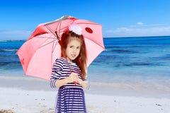 Bambina che si nasconde sotto un ombrello fotografia stock libera da diritti
