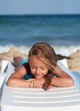 Bambina che si rilassa su una sedia di spiaggia fotografie stock