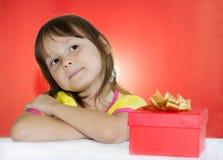 Bambina che si siede accanto al contenitore di regalo Immagini Stock Libere da Diritti