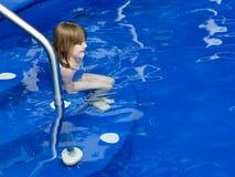 Bambina che si siede in acqua bassa sui punti di uno stagno blu profondo fotografia stock libera da diritti