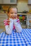 Bambina che si siede ad una tavola con un panno blu Fotografie Stock