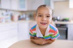 Bambina che si siede ad una tavola ed a sorridere Immagini Stock