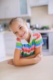 Bambina che si siede ad una tavola ed a sorridere Fotografia Stock Libera da Diritti