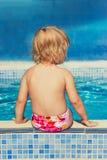 Bambina che si siede al bordo dello stagno fotografia stock libera da diritti
