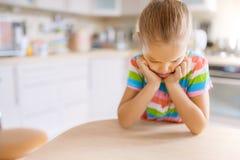 Bambina che si siede alla tavola e triste Immagini Stock Libere da Diritti
