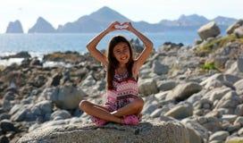 Bambina che si siede alle rocce alla parte anteriore di oceano nel mare della scogliera della località di soggiorno di Los Cabos  Immagini Stock