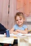 Bambina che si siede allo scrittorio del banco Immagini Stock