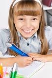 Bambina che si siede allo scrittorio nell'aula Fotografia Stock Libera da Diritti