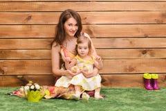 bambina che si siede con la mamma ed i pulcini immagini stock