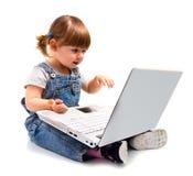 Bambina che si siede con un computer portatile Fotografia Stock