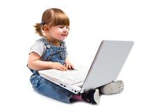 Bambina che si siede con un computer portatile Immagine Stock Libera da Diritti