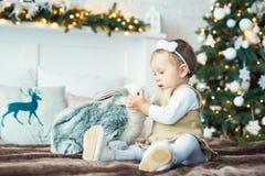 Bambina che si siede con una lepre sui precedenti degli alberi Buon Natale Immagine Stock