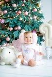 Bambina che si siede con una lepre sui precedenti degli alberi Buon Natale Immagini Stock Libere da Diritti