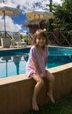 Bambina che si siede dal bordo dello stagno Fotografia Stock Libera da Diritti