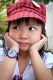 Bambina che si siede la sua mano sul mento immagine stock libera da diritti