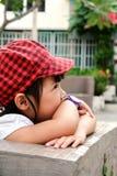 Bambina che si siede la sua mano sul mento immagini stock libere da diritti