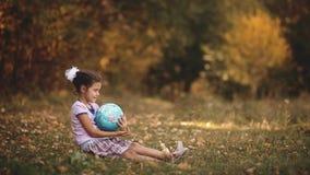 Bambina che si siede nell'azienda forestale di autunno un globo viaggio di geografia della bambina piccolo bambino felice, neonat video d archivio