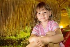 Bambina che si siede nella vecchia baracca Fotografia Stock