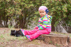 Bambina che si siede su un ceppo Immagine Stock