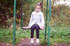 Bambina che si siede su un'oscillazione Immagine Stock