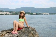 Bambina che si siede su una roccia entro le vacanze estive del mare fotografie stock libere da diritti