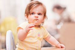 Bambina che si siede su una sedia di legno fotografia stock
