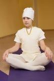 Bambina che si siede su una stuoia di yoga nella palestra Fotografia Stock Libera da Diritti