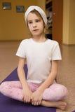 Bambina che si siede su una stuoia di yoga nella palestra Fotografie Stock Libere da Diritti