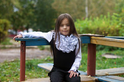 Bambina che si siede sul campo da giuoco Fotografie Stock Libere da Diritti