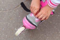 Bambina che si siede sul parapetto e che mette sui rulli nel parco Fotografia Stock Libera da Diritti