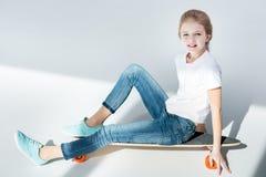 Bambina che si siede sul pattino e che esamina macchina fotografica fotografia stock