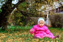 Bambina che si siede sul prato inglese in autunno fotografia stock