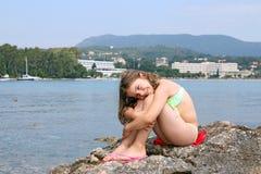 Bambina che si siede sulla roccia vicino al mare Fotografie Stock