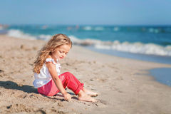 Bambina che si siede sulla spiaggia in pantaloni rosa fotografie stock libere da diritti