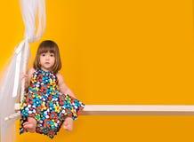 Bambina che si siede sulle oscillazioni all'interno fotografie stock libere da diritti