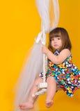 Bambina che si siede sulle oscillazioni all'interno fotografia stock libera da diritti