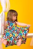 Bambina che si siede sulle oscillazioni all'interno immagine stock libera da diritti