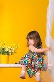 Bambina che si siede sulle oscillazioni con i fiori all'interno immagine stock
