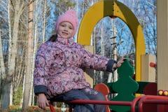 Bambina che si siede sullo scorrevole al campo da giuoco ed ai sorrisi Fotografia Stock Libera da Diritti