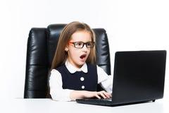 Bambina che si siede sullo scrittorio nel suo luogo di lavoro vestito come donna di affari immagini stock libere da diritti