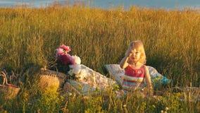 Bambina che si siede in un campo su una coperta archivi video
