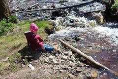 Bambina che si siede vicino ad un fiume della montagna fotografia stock libera da diritti