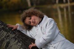 Bambina che si siede vicino ad un lago Fotografia Stock