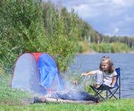 Bambina che si siede vicino al fuoco di accampamento Pane di torrefazione della ragazza sopra fuoco di accampamento fotografia stock libera da diritti